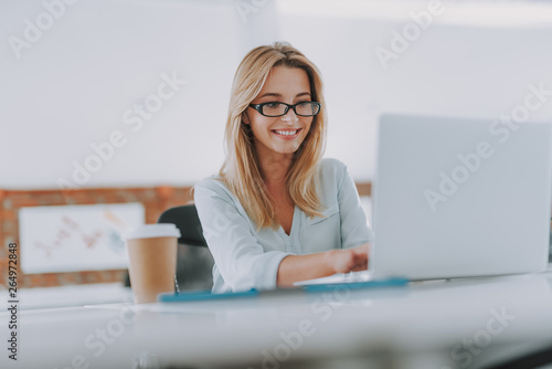 Fotografia  Cheerful young woman smiling while using laptop at work