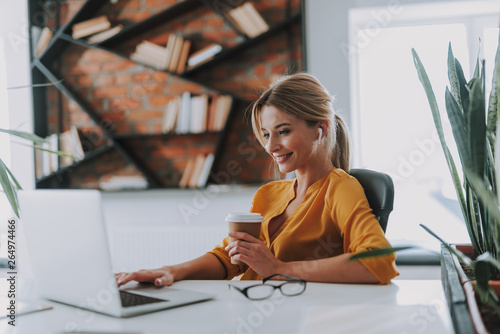 Positive businesswoman in her office working on the laptop