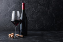 Elegant Glass And Bottle Of Red Wine With Corks And Corkscrew On Black Stone Background. Natural Light