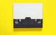 canvas print picture - The videotape in a paper case on on yellow background. Pop culture attributes, minimalism. Top view