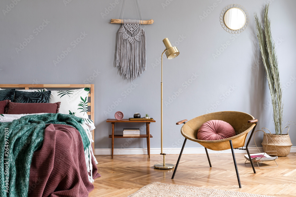 Fototapety, obrazy: Stylish and luxury interior of bedroom with design furnitures, honey yellow armchair, gray macrame on the walls and elegant accessories. Beautiful bed sheets, blankets and pillows. Warm home decor.