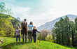 canvas print picture - family on a green meadow looking at the mountain panorama