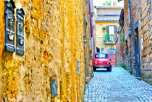 View Of A Small Car In The Historic Cityscape In Orvieto, Italy With Vintage And Isolated Color Effect.
