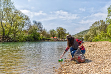 Woman Volunteer Helps Clean The Shore Of River Of Garbage. Earth Day And Environmental Improvement Concept