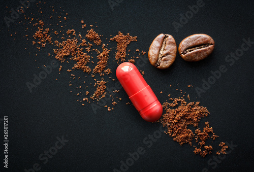 red pill and coffee beans on a black background, the concept of drugs containing Fototapeta