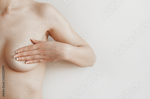 Fotografie, Obraz Closeup cropped portrait young woman with breast pain touching chest colored iso