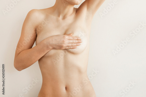 Obraz na plátně Closeup cropped portrait young woman with breast pain touching chest colored iso