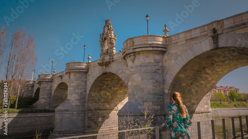 A young woman is standing in front of the medieval Toledo old limestone bridge or Puente de Toledo downtown Madrid, Spain at Madrid Rio across the Manzanares river on a warm spring day Canvas Print