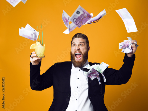 Fototapeta Happy young businessman with glass of cocktail in formal clothes holding bunch of money banknotes obraz