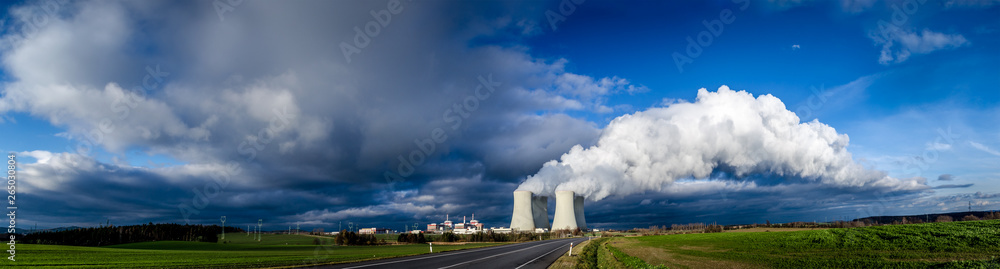 Fototapety, obrazy: Nuclear plant and its cooling towers releasing a huge cloud of steam to the sky. Verdant vegetation around.