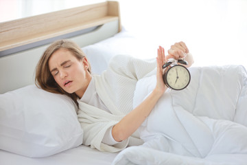 beautiful and healthy young women does not want to wake up and try to stop alarm clock on the bed with unhappy face