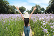 back view portrait of beautiful woman having a happy time and enjoying among flower Naga-crested field in nature
