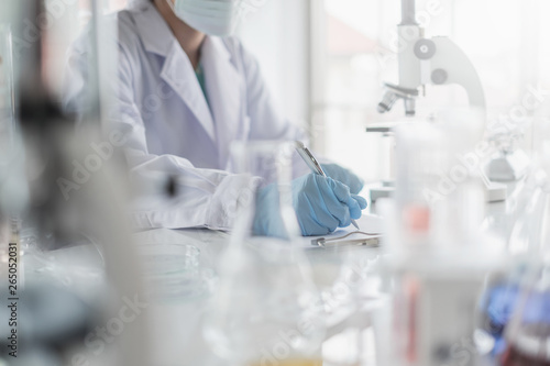Fotografía  A scientist hands writing on a clipboard in laboratory with test tube microscope and solutions