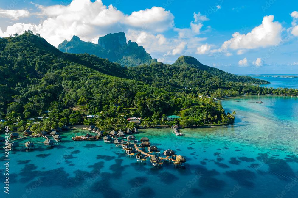 Fototapeta Bora Bora aerial drone video of travel vacation paradise with overwater bungalows luxury resort, coral reef lagoon ocean beach. Mount Otemanu, Bora Bora, French Polynesia, Tahiti, South Pacific Ocean