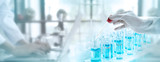 Fototapeta Coffie - Test tubes with liquid in laboratory, Doctor hand holding dropper with dripping or transparent glass pipette, dropper for instillation. scientist working in laboratory. Banner for website adverting.