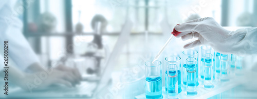 Test tubes with liquid in laboratory, Doctor hand holding dropper with dripping or transparent glass pipette, dropper for instillation. scientist working in laboratory. Banner for website adverting.