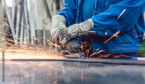 Fotografia Worker in metal factory grinding workpiece with sparks flying