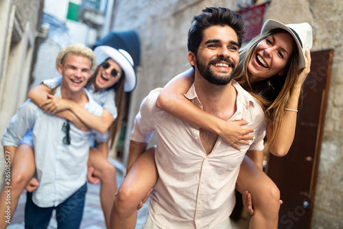 Photo Happy friends enjoying piggyback while sightseeing in the city.