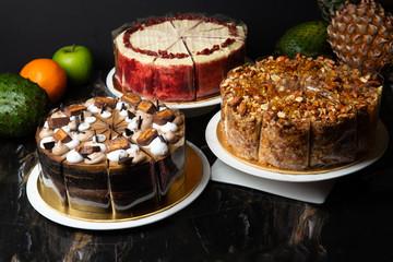 izloženi razni kolači s tamnom pozadinom