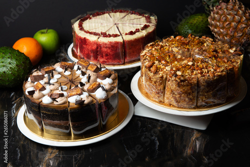 various cakes on display with dark background