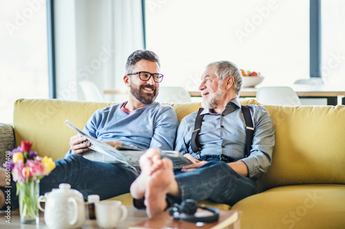Fotografie, Obraz  An adult hipster son and senior father sitting on sofa indoors at home, talking