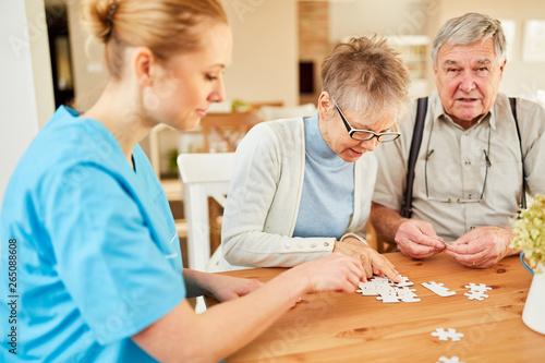 Foto  Pflegekraft und Senioren Paar beim Puzzle spielen