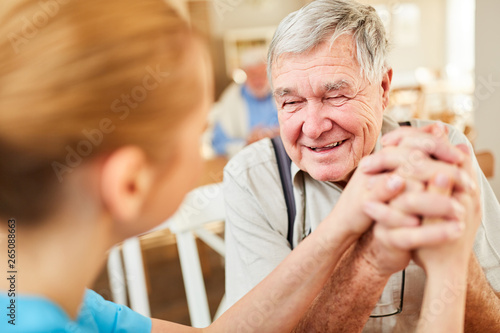 Leinwand Poster Pflegedienst tröstet Senior Mann bei Hausbesuch