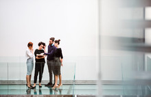 Group Of Young Businesspeople Standing Near Staircase, Talking.