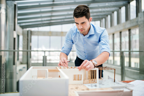 Young businessman or architect with model of a house standing in office, working Canvas Print