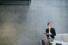 Young Business Woman With Tablet Sitting On Desk Against Concrete Wall In Office.