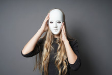 Mysterious Young Woman Adjusting Her Mask With Her Hands