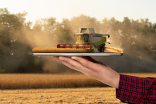 Farmer Holding A Tablet With A Combine Harvester. Augmented Reality And Digital Transformation In Agriculture. Smart Farming Concept