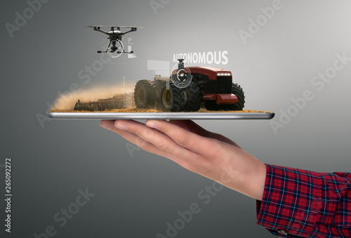 Aufkleber - Farmer holding a tablet with autonomous tractor and drone. Smart farming