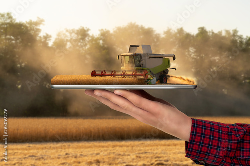 Aufkleber - Farmer holding a tablet with a combine harvester. Augmented reality and digital transformation in agriculture. Smart farming concept
