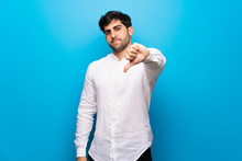 Young Man Over Isolated Blue Wall Showing Thumb Down Sign With Negative Expression