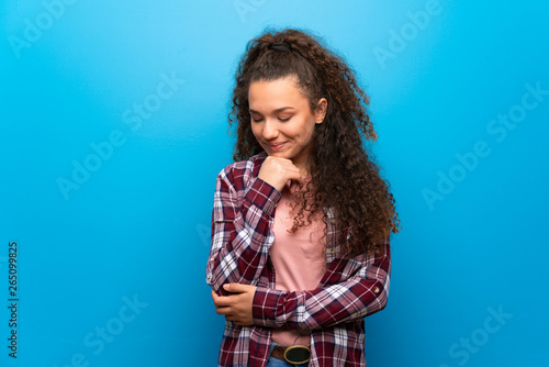 Fotografiet  Teenager girl over blue wall looking down with the hand on the chin