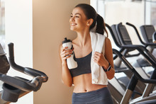 Feeling Happy. Young And Beautiful Woman In Sportswear With White Towel On Her Shoulders Is Holding Bottle Of Water And Smiling While Standing In Front Of Windows At Gym.