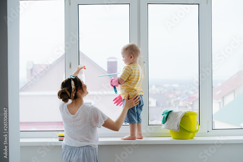 Fotografia  Funny little blond toddler boy is cleaning plastic window door with scrubber