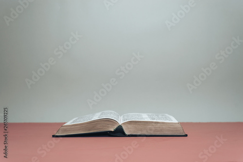 Fotografie, Obraz  Open Holy Bible on a red table.  Grey wall background..