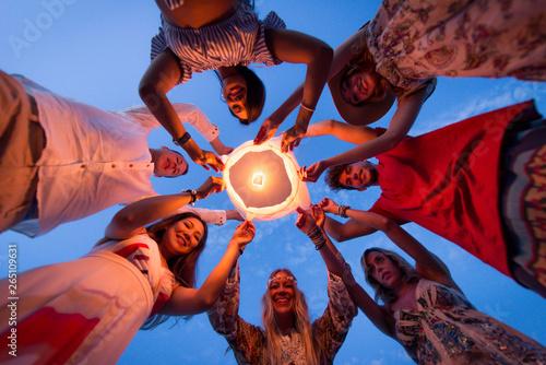 Group of friends lighting lanterns Canvas Print