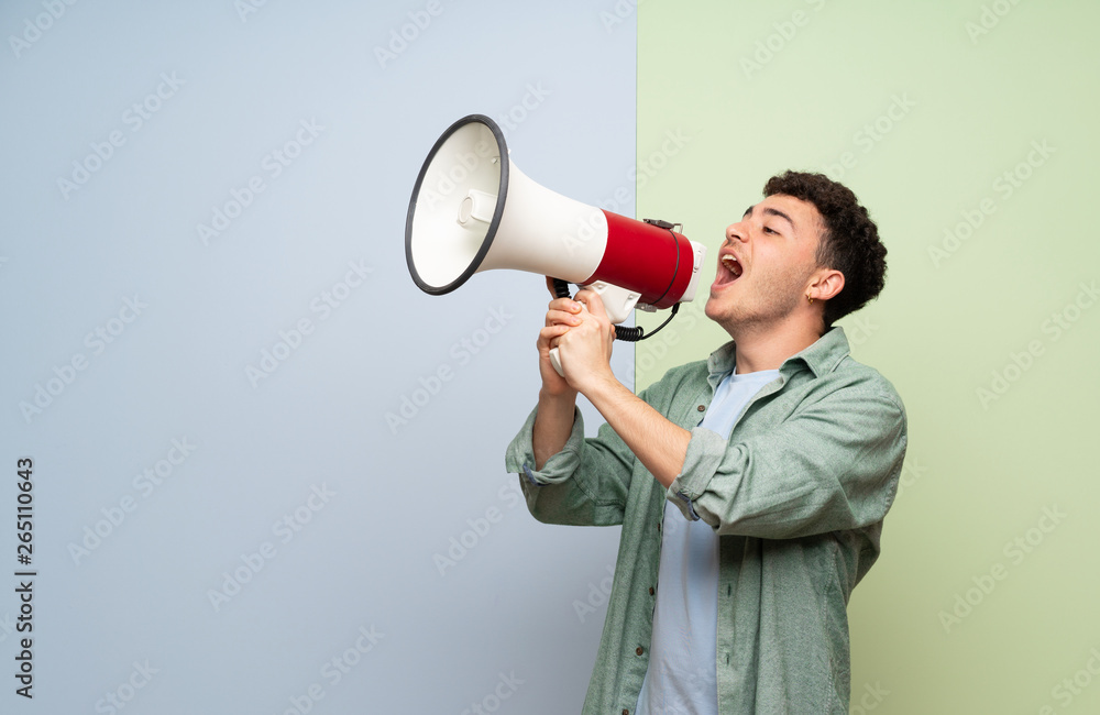 Fototapeta Young man over blue and green background shouting through a megaphone