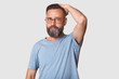 canvas print picture - Middle aged good looking bearded man with fashionable spectacles wearing light blue casual t shirt, stands in front of camera, looking at it. hard working model poses isolated over light background.