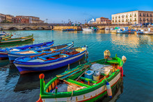 Colorful And Bright Close Up Fishing Boats On Water In The Bay Of The Island Ortigia, Syracuse In Sicily, South Italy
