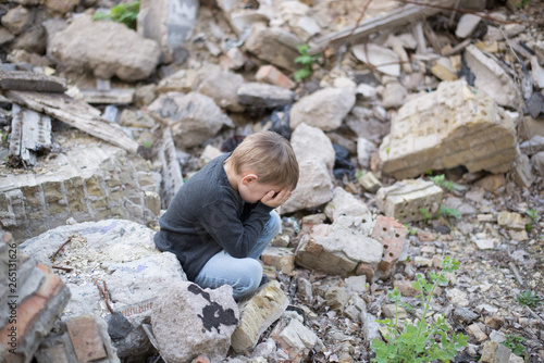 Photo boy crying among the ruins