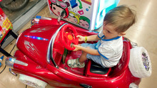 Little Toddler Boy Having Fun In Amusement Park. Child Riding On Insert Coin Electric Car At Shopping Mall