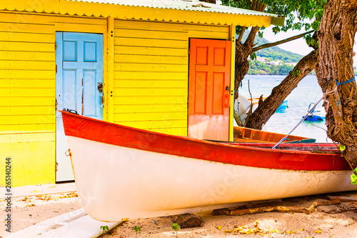 Obraz na plátne Beautiful bright colored wooden house on sea side with colorful wooden boat in front