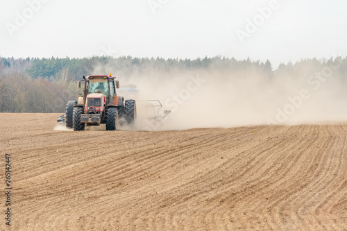 Fotomural  Farmer in tractor preparing land with seedbed cultivator as part of pre seeding activities in early spring season of agricultural works at farmlands