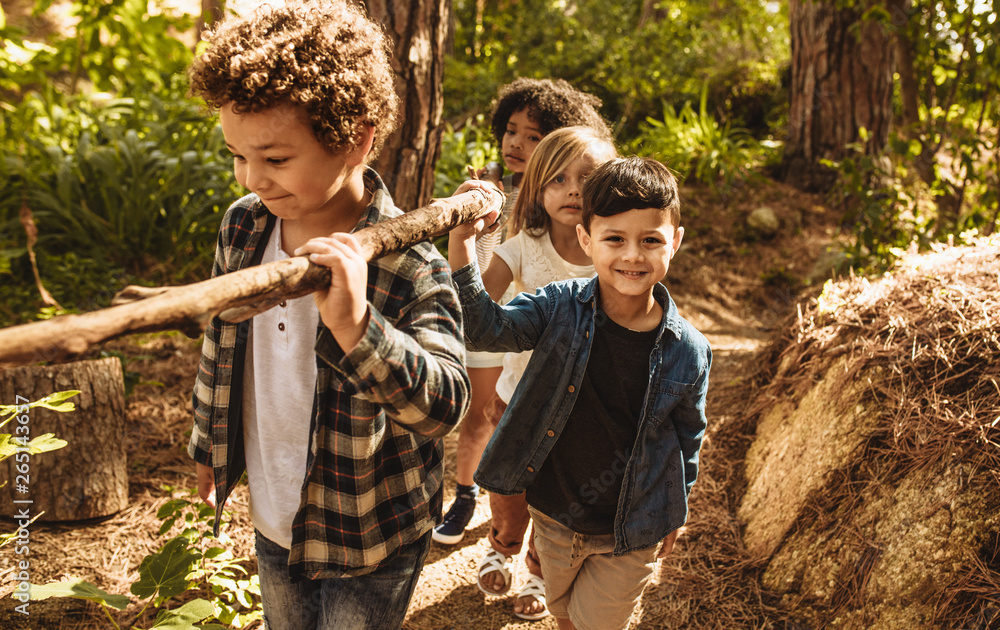 Fototapety, obrazy: Kids making camp in forest