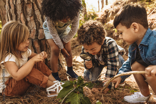 Photo Kids exploring in forest with a magnifying glass