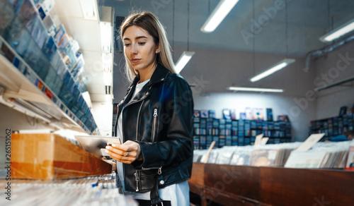 Spoed Foto op Canvas Muziekwinkel Young attractive woman choosing vinyl record in music record shop.